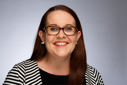 Morwenna smiling at the camera, wearing a black and white striped jacket over a black top, tortoise shell rimmed glasses and gold earrings, with long brown hair flowing over her shoulders.