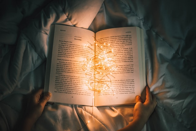 In a darkened space hands holding an open book lis by a cluster of small lights