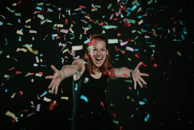 A smiling person with hands out wide amongst multi-coloured, falling squares of paper