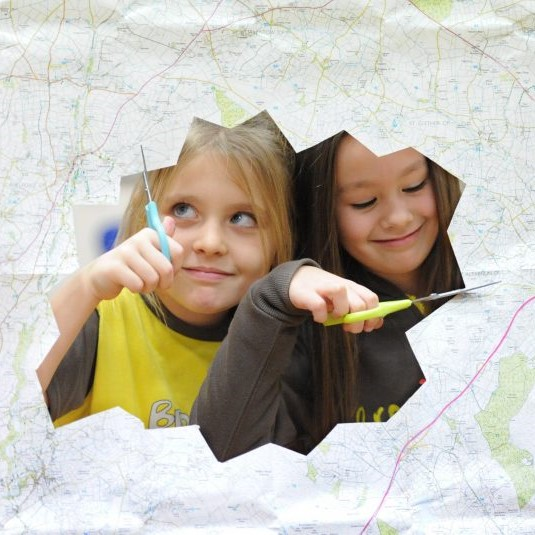 Two smiling children peek through a jagged hole they are cutting from a sheet of paperthey