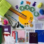 A selection of many scrapstore bits and pieces including string, balloons, rubber bands, feathers, silver stars, paperclips, card and paper of various sizes, colours and shapes, straws, felt shapes and a pencil.