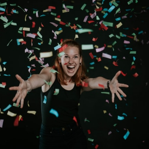 A smiling woman with arms out stretched is covered by falling strips of coloured paper