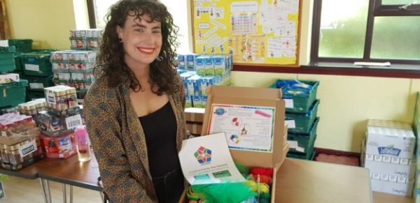 A smiling woman with long, curly hair stands in front of a table withfood to distributeholding an arts pack