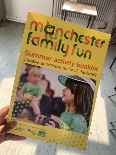 A hand holds a colourful family activity booklet. The cover of the booklet shows a smiling child wearing a green sun visor and playing a concertina.small mu