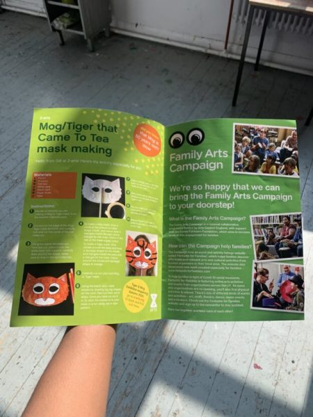 A hand holds anopen family fun activity brochure.