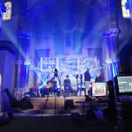 Band playing on a stage in a church.