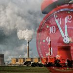 A huge red alarm clock with hands at five to twelve looms over industrial chimneys spewing out smoke