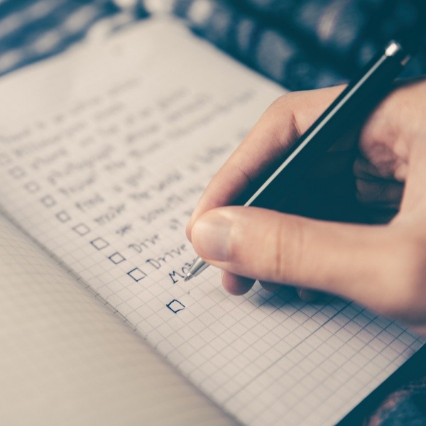 A hand holds a pen and ticks off a box on a checklist
