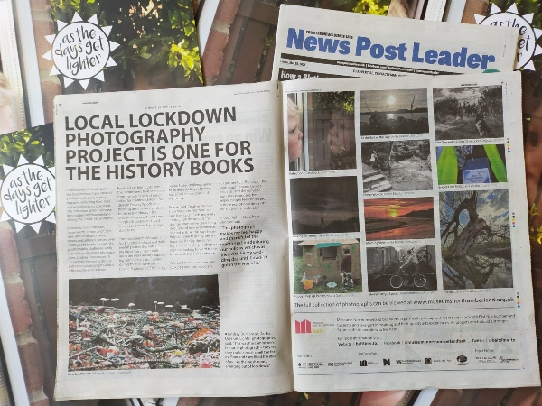 An open newspaper with a double page spread on As the Days Get Lighter photography project