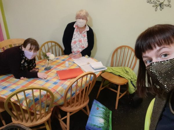 three women of different ages, all wearing face masks around a kitchen table