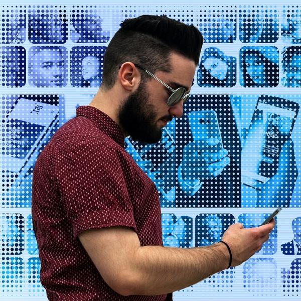 A beardedmanwearing dark glasses looks at his phone.