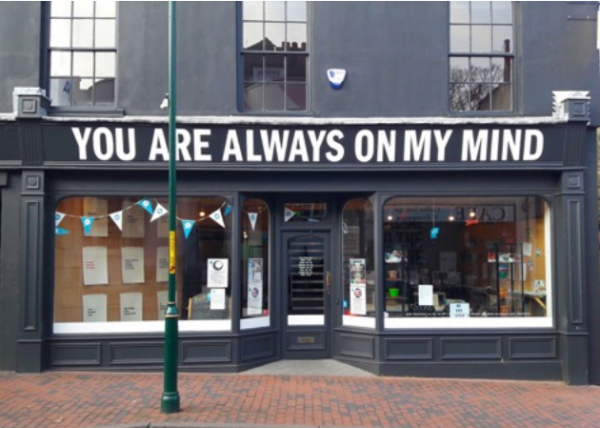 A double fronted shop with a door in the middle and bunting on the window. A large sign spans the whole shop front saying: you are always on my mind