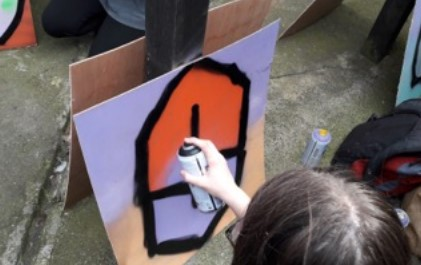 A participant at a graffiti workshop stands in front of an easel spraying paint onto a large board