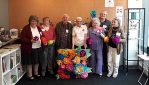 A group of 7 older people stand in a row behinda large crafted collagemade from brightly coloured paper. .