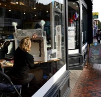 An artist sits drawing in the shop front window