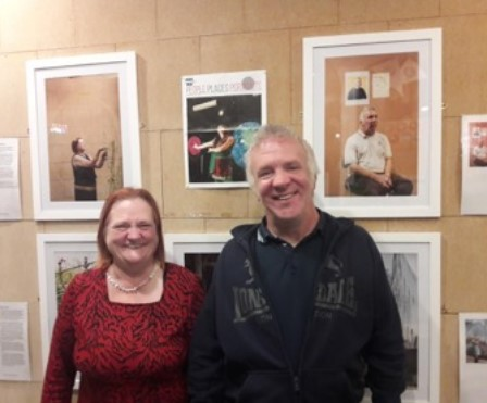 A smiling man and woman stand in front of a wall full of framed photographs.