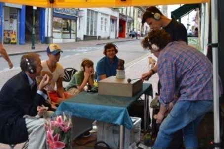 A table on the pavement in front of the shop is used for a performance.