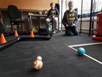 two young boys, one lounging on a chair, one kneeling on the carpe. Both have game controllers and are moving objects on the carpet.