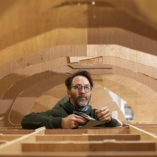 Image of a man building inside an boat hull