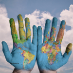 A pair of hands painted blue with a world map crossing both hands