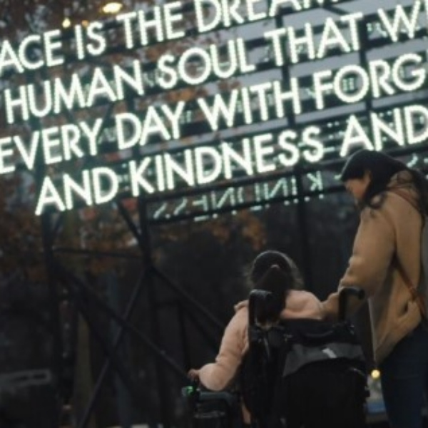A mother looks down at her daughter who is in a wheelchair. They are stood in front of a large, illuminated sign.