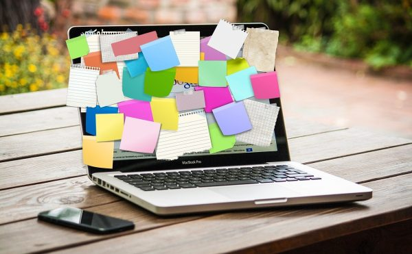 An open laptop. The screen is covered with different coloured post-it notes of various sizes