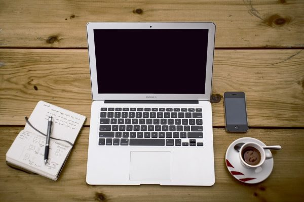 Anopenlaptop, smart phone, notepad and pen and a cup of coffee