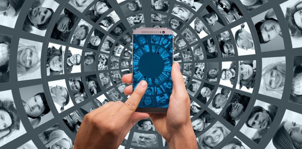 A finger touches a smart phone against a backdrop of a myriad of faces
