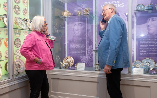 A lady in a pink jacket and a man in a blue jacket smile whilst holding an audio guide and looking at ceramic plates, teapots and models of cats commissioned by Lord Admiral Nelson