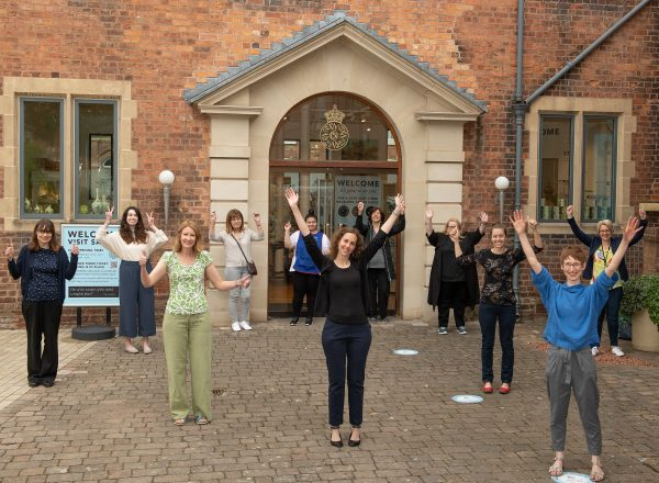 Eleven members of staff stand outside the entrance to the Museum of Royal Worcester and hold their arms aloft to celebrate reopening the museum