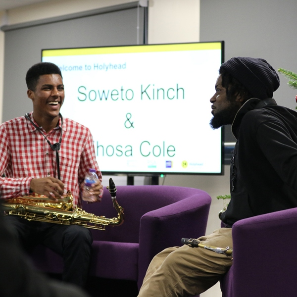 Two musicians sit talking in front of a large screen