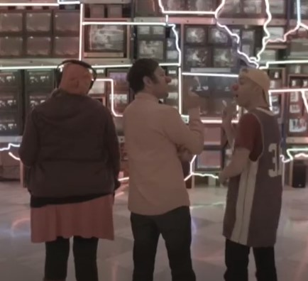 The backsof three people looking at a large digital exhibit. One is wearing a headset. The other two are engaged in animated conversation.