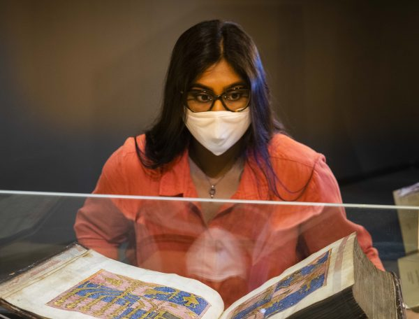 Visitor in mask looking at manuscript in the British Library