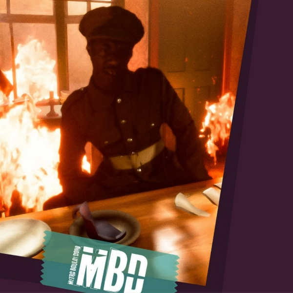 A soldier sits at a table set for dinner. He seems unconcerned as flames surround him.