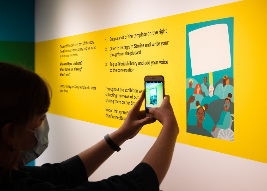 Visitor to British Library taking photo of exhibit with mobile phone