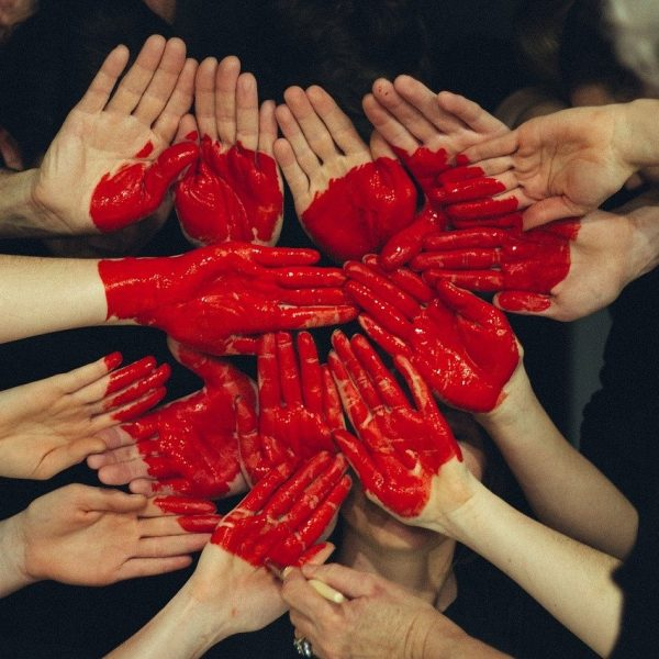 14 hands thrust together. Another hand holds a red felt pen and is finishing colouring one of the hands to make a heart.