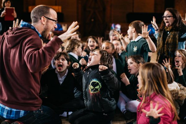 Adult at left hand side of image has hands in the air with group of children with excited faces