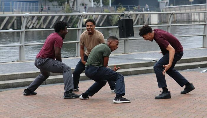 Group of 4 dancers on pavement next to railings by a river