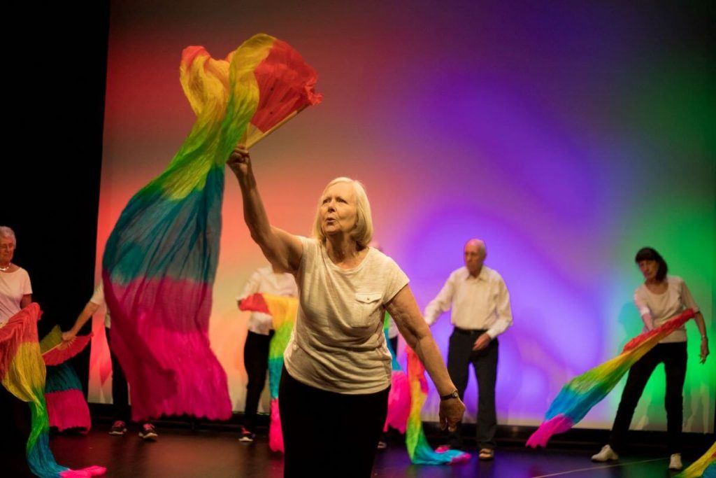 Group dancing on a stage with rainbow-coloured material. Person in foreground holding material above their head.
