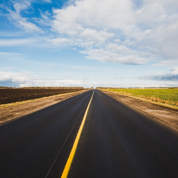 A wide, long road with a single yellow line heading into the distance. Fields are either side and there's a blue sky with a few white clouds